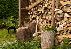 Log store with Wheelbarrow, leaves and stump Royalty Free Stock Photography