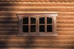 Log wall with one centered window. Log wall with one centered rectangular window under sunlight with blurry shadows Stock Photo
