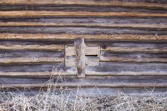 A log wall of a wooden old house. With a boarded up window Stock Photo