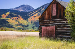 A log wooden barn at Twin Lakes Colorado area. A old vintage log cabin wooden barn at Twin Lakes Colorado area. with the fall landscape and mountains in the Stock Image
