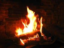 Logboekbrand in open baksteenopen haard Stock Fotografie