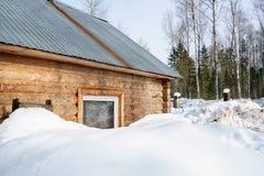 Logboekhuis met sneeuw in bos wordt behandeld dat Stock Afbeeldingen