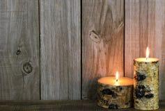 Logboekkaarsen die door doorstane houten achtergrond branden Stock Fotografie
