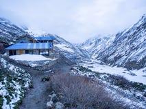 Loge bleue de toit sur la montagne de neige et village à la distance Images stock