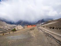 Loge rouge avec le temps banni à la montagne à la distance derrière Photo libre de droits