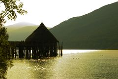 Logement antique de loch de Crannog, coucher du soleil images stock