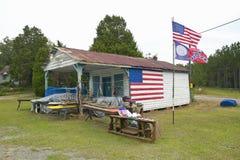 Logement rustique avec les drapeaux américains et confédérés le long de la route 22 en Géorgie centrale Photographie stock libre de droits