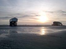 Logements de pile au coucher du soleil près de St Peter ording à marée basse Images libres de droits