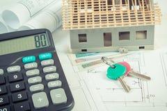 Logez en construction, des clés, calculatrice et polissez l'argent de devise sur les dessins et les diagrammes électriques Photo libre de droits