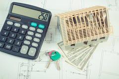 Logez en construction, les clés, la calculatrice et le dollar de devises sur les dessins et les diagrammes électriques Images libres de droits