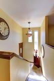 Logez l'intérieur, couloir de niveau fendu de jaune avec l'horloge Images libres de droits