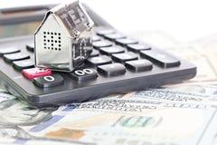 Logez le modèle, la calculatrice et l'argent américain d'argent liquide du dollar sur la table de bureau Photographie stock libre de droits