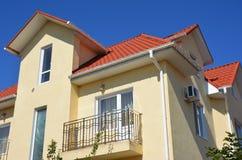 Logez le toit rouge en métal avec la fenêtre de grenier, balcon, domaine problématique de réseau de pipe-lines de gouttières Gout photographie stock libre de droits