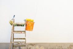 Logez les accessoires de rénovation, d'échelle et de peintre devant un mur Photographie stock libre de droits