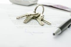 Logez les clés sur un contrat de vente de maison Image libre de droits