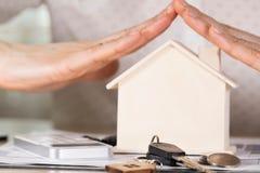 Logez les clés et les pièces de monnaie devant une maison en bois Photo stock
