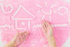 Logez les mains peintes du ` s d'enfants sur le sable décoratif Photographie stock