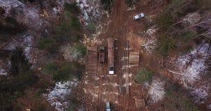 Logga lastbilen som laddas med nytt sågad timmer, lämnar den logga platsen i taigaen arkivfilmer