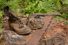 Logging boots and handsaw Royalty Free Stock Image