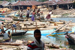 Logging business number 2. Men working at a sawmill in Bangladesh making sure the logs are moved up from the water Stock Image
