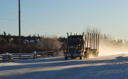 Logging truck. Fast driving logging truck on the highway in winter royalty free stock photo