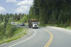 Logging truck and cars moving on highway 18 Stock Images