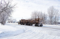 Logging truck. An eighteen wheel truck hauling a load of cut logs down a street through a small town in winter Royalty Free Stock Photos