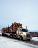 Logging truck snow. A side view of a large logging truck in the snow Stock Image