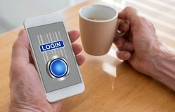 Login concept on a smartphone. Male hands holding a smartphone with login concept and a cup of coffee royalty free stock image