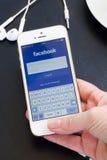 Loging在Iphone5s的Facebook app在指纹帮助下。 库存照片