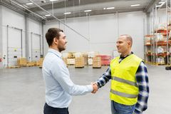 Worker and businessman with clipboard at warehouse. Logistic business and cooperation concept - manual worker and businessman with clipboard shaking hands and Stock Photo