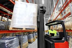 Loader operating forklift at warehouse. Logistic business, shipment and loading concept - loader with clipboard and cargo on forklift at warehouse Royalty Free Stock Image