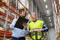 Businessman with clipboard and loader at warehouse. Logistic business, shipment and people concept - businessman with clipboard and warehouse worker with loader Stock Photo