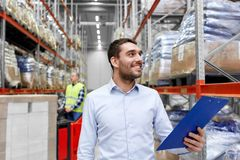 Happy businessman with clipboard at warehouse. Logistic business, shipment and people concept - happy businessman with clipboard and worker loading goods by Royalty Free Stock Image