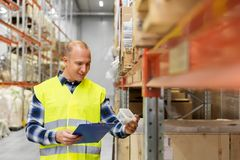 Warehouse worker with clipboard and plastic box. Logistic business, shipment and people concept - male worker with clipboard and plastic box in reflective safety Royalty Free Stock Images