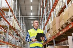 Warehouse worker with clipboard in safety vest. Logistic business, shipment and people concept - male worker or supervisor with clipboard in reflective safety Royalty Free Stock Image
