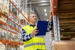 Warehouse worker with clipboard in safety vest. Logistic business, shipment and people concept - male worker or supervisor with clipboard in reflective safety Stock Photography