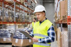 Warehouse worker with clipboard in safety vest. Logistic business, shipment and people concept - male worker or supervisor with clipboard in reflective safety Royalty Free Stock Photo