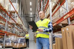 Warehouse worker with clipboard in safety vest. Logistic business, shipment and people concept - male worker or supervisor with clipboard in reflective safety Stock Photos