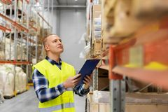 Warehouse worker with clipboard in safety vest. Logistic business, shipment and people concept - male worker or supervisor with clipboard in reflective safety Royalty Free Stock Photography