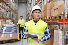 Warehouse worker with clipboard in safety vest. Logistic business, shipment and people concept - smiling male worker or supervisor with clipboard in reflective Royalty Free Stock Photography