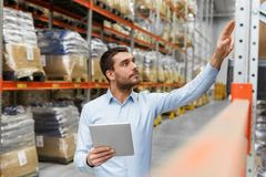 Businessman with tablet pc at warehouse. Logistic business, technology and shipment concept - businessman with tablet pc computer checking goods at warehouse Stock Photo