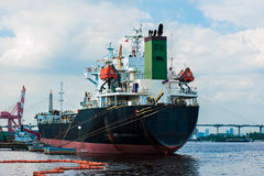 Logistic concept, black Ship parked in the river. Waiting to dock and load the goods royalty free stock photography