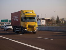 Logistic container container on Scania truck. Logistic container on yellow scania truck on italian motorway A4 on Milano direction Royalty Free Stock Image