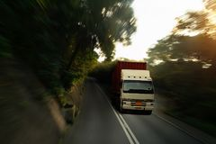 Logistic by Container truck driving in motion blur on the road. At sunset Royalty Free Stock Photo