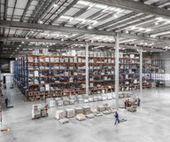 Logistic shed and distribution boxes workers and forklift in operation. Rack royalty free stock photo