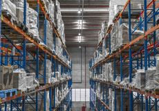 Logistic shed and distribution boxes workers and forklift in operation. Rack stock images