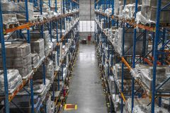 Logistic shed and distribution boxes workers and forklift in operation. Rack royalty free stock image
