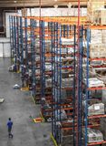 Logistic shed and distribution boxes workers and forklift in operation. Rack royalty free stock images