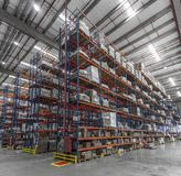 Logistic shed and distribution boxes workers and forklift in operation. Rack stock image